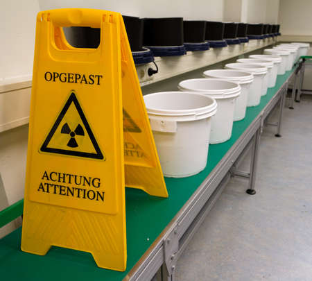 radioactivity: A sign warning for radioactivity on a conveyor belt with buckets for transport behind it