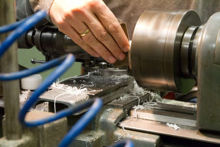 Close up of a man working on a lathe photo