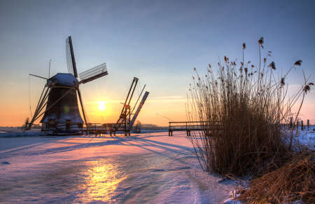 Beautiful sunset behind an old mill in winter in the Netherlands, HDR photo