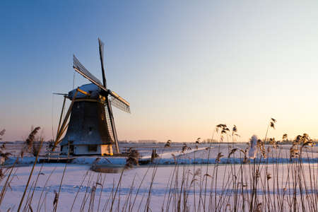 Old wind mill at a frozen river in winter in the Netherlands photo