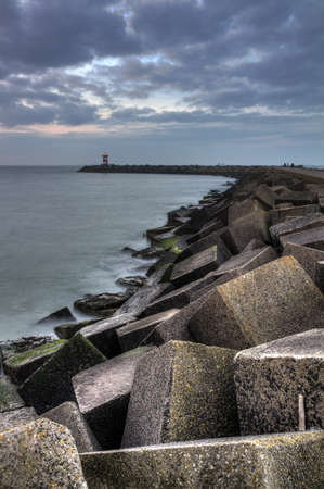 HDR image of the concrete blocks which form the jetty on a cloudy day at sunset in Scheveningen, Netherlands
