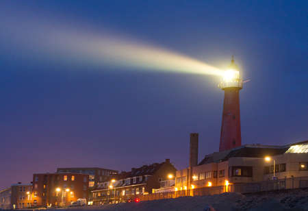 Lighthouse shines a beam of bright light towards the sea at twilight in Scheveningen, Netherlands Publikacyjne