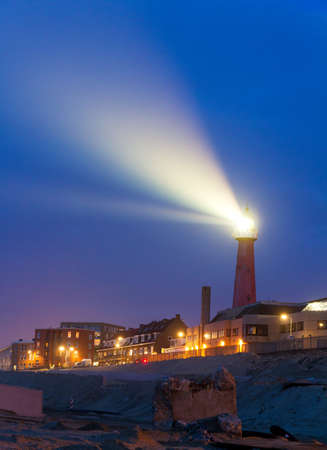 Lighthouse shines a beam of bright light into the night in Scheveningen, Netherlands