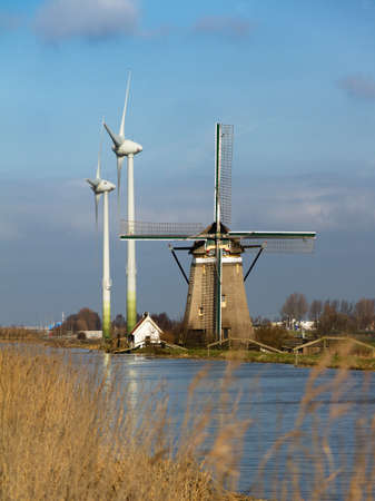 An old traditional dutch windmill with 2 very large modern wind turbines in the background at the river photo
