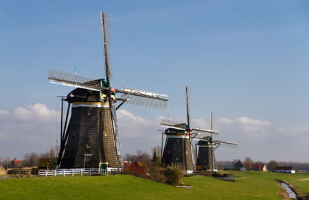 Three dutch windmills in a row on a sunny day photo