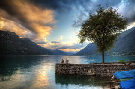 Two old men are fishing on the shore of the brienzersee in Switzerland at sunset  HDR