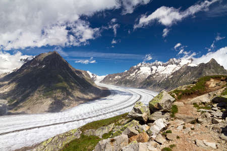 aletsch: Beautiful panorama of the breathtaking Aletsch glacier as seen from the Bettmer alp in switserland, on a sunny day with clouds in summer