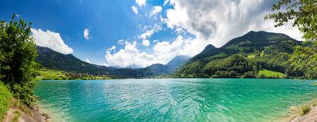 Immagine panoramica dalla riva di un lago di montagna verde e blu nelle Alpi svizzere