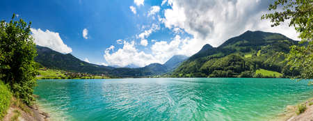 Panoramic image from the shore of a Green and Blue Mountain lake in the Swiss Alps photo