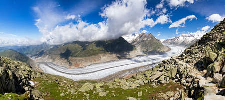 polarised: Large panorama of the breathtaking Aletsch glacier as seen from the Bettmer alp in switserland, on a sunny day with clouds in summer