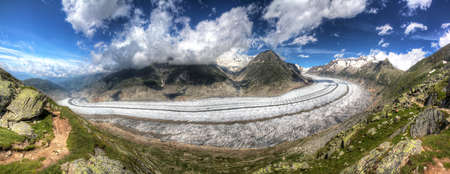 polarised: Beautiful panorama of the breathtaking Aletsch glacier as seen from the Bettmer alp in switserland, on a sunny day with clouds in summer  HDR Stock Photo
