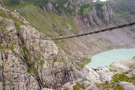 Trift Bridge is the longest pedestrian-only suspension bridge in the Alps, totaling 170 metres  560 ft  in length and traversing a height of 100 metres  330 ft   The bridge spans the lake, Triftsee, near Gadmen, Switzerland Stock Photo - 15316602