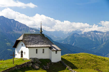 Little church in the mountains of the Swiss alps on a beautiful day photo
