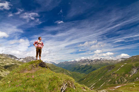 Young explorer in traditional clothing stands proud on top of a mountain in the Swiss Alps on a sunny summer day photo