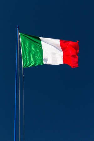 Large Italian flag waving in the wind against a dark blue sky photo