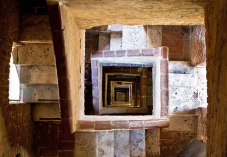 Looking down the stairs in the high Torre del Mangia in Siena, Italy photo