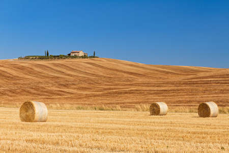 Typical tuscan landscape with hay bales and golden fields and a farm on top of the hill photo