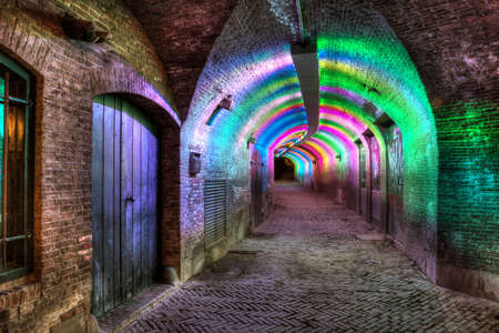 Lower passage tunnel at a moat in Utrecht, Netherlands, lit in different colors