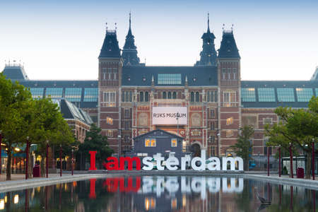 The national state museum and the IAMsterdam sign reflecting in the pond early in the morning in Amsterdam, the Netherlands Editorial
