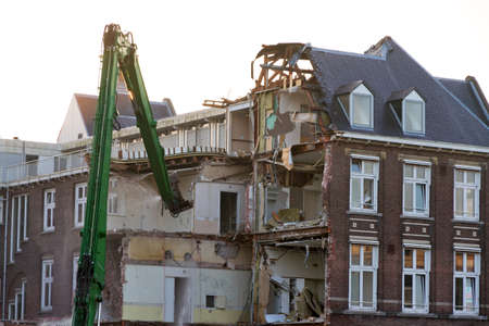 Big crane demolishing an old house in Amsterdam, the Netherlands