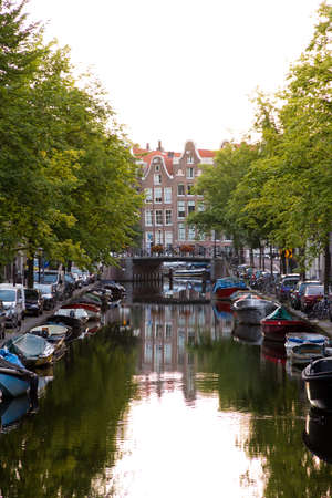 Typical view on a canal in Amsterdam, the Netherlands, with townhouses at the end