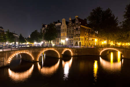 Beautiful view on a canal in Amsterdam at night with lights on the bridges