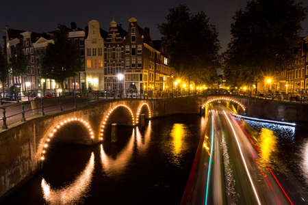 Stripes of light of a tourboat passing by on a canal in Amsterdam at night Stock Photo - 16782561