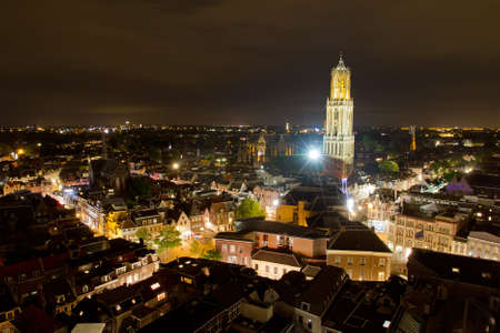 Cityscape of the city of Utrecht at night with the Dom cathedral lit by big lights photo
