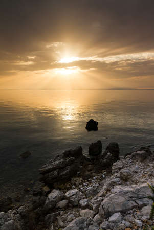polarised: Beautiful sunset with clouds, a calm sea and a rocky shore in Croatia