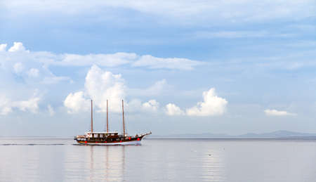 Beautiful ship sailing on a calm sea with a nice cloudscape photo
