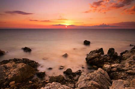 Beautiful colored sunset at the rocky coast of Croatia photo
