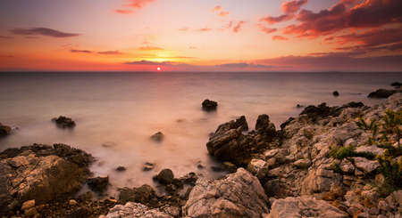Beautiful colored sunset panorama at the rocky coast of Croatia photo