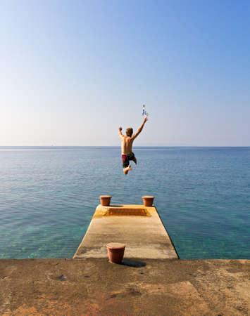 man jump: Running of a pier jumping into the sea being free in summer Stock Photo