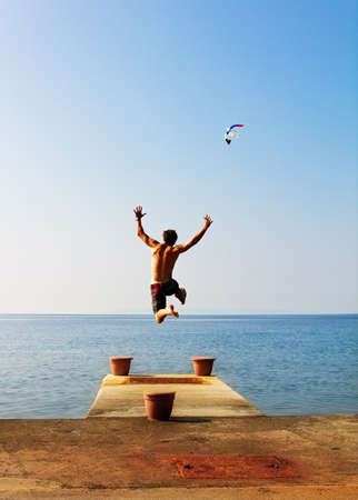 Running of a pier jumping into the sea being free in summer Stock Photo
