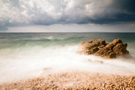 Long exposure image of a rocky beach in Croatia with a big rock in the sea photo