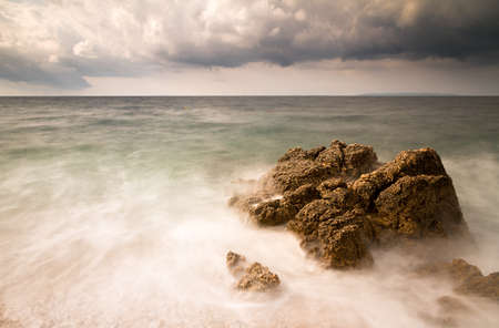polarised: Long exposure image of a stormy beach in Croatia with a big rock in the sea Stock Photo