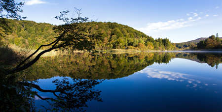 Beautiful panoramic view of a calm lake at Plitvice national park in Croatia, early in the morning photo