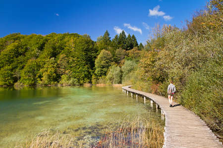 Woman walking on the wooden footpath near a lake in Croatia in autumn photo