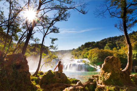 Beautiful woman sits at the waterfall in Krka national park, Croatia photo