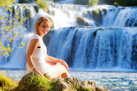 Stunning young woman sitting at a waterfall in Krka national park  Wearing a white dress in summer, smiling lovely over her shoulder photo