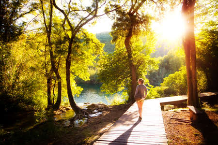 Beautiful young woman walks in Krka national park in Croatia at sunset photo