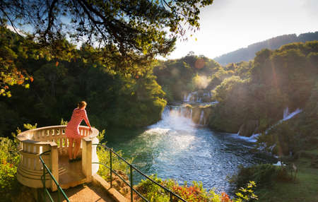 Young woman looks over the waterfalls of the Krka river in Krka national park in Croatia Stock Photo