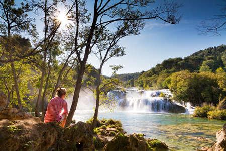 Beautiful woman sits at the waterfall in Krka national park, Croatia Stock Photo