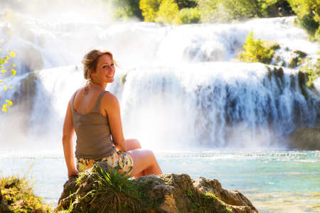 Stunning young woman sitting at a waterfall in Krka national park, smiling lovely over her shoulder photo