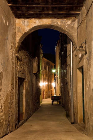Mediterranean alley with an arched gate in a small town at night photo