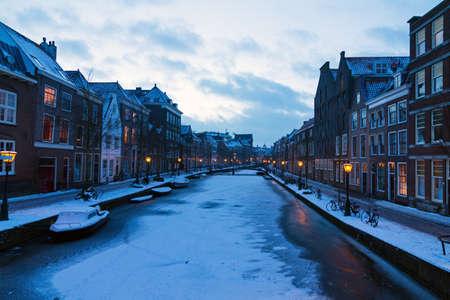 Frozen river Rhine Oude rijn at twilight in Leiden in the Netherlands