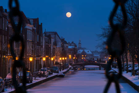 Oude Rijn in Leiden, the Netherlands  A full moon rises over the city canal seen through the chain bars of the Kerkbrug Stock Photo - 19199363
