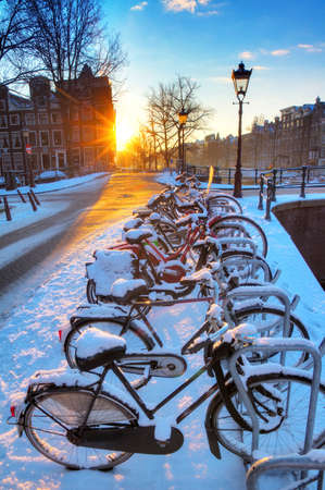 Sunrise over the canal streets of Amsterdam, the Netherlands, with bicycles covered in snow on a beautiful winter day  HDR