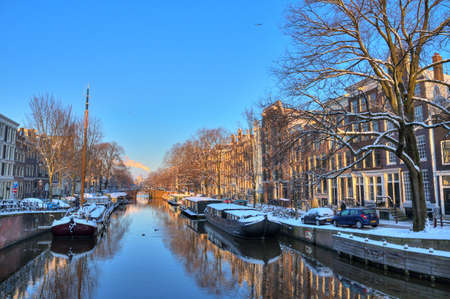 Beautiful early morning winter view on one of the city canals of Amsterdam, The Netherlands  HDR