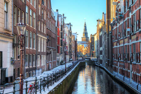 Winter cityscape of the Oudezijds kolk in Amsterdam, the Netherlands, with the Oude Kerk old church, 1213 in the background HDR